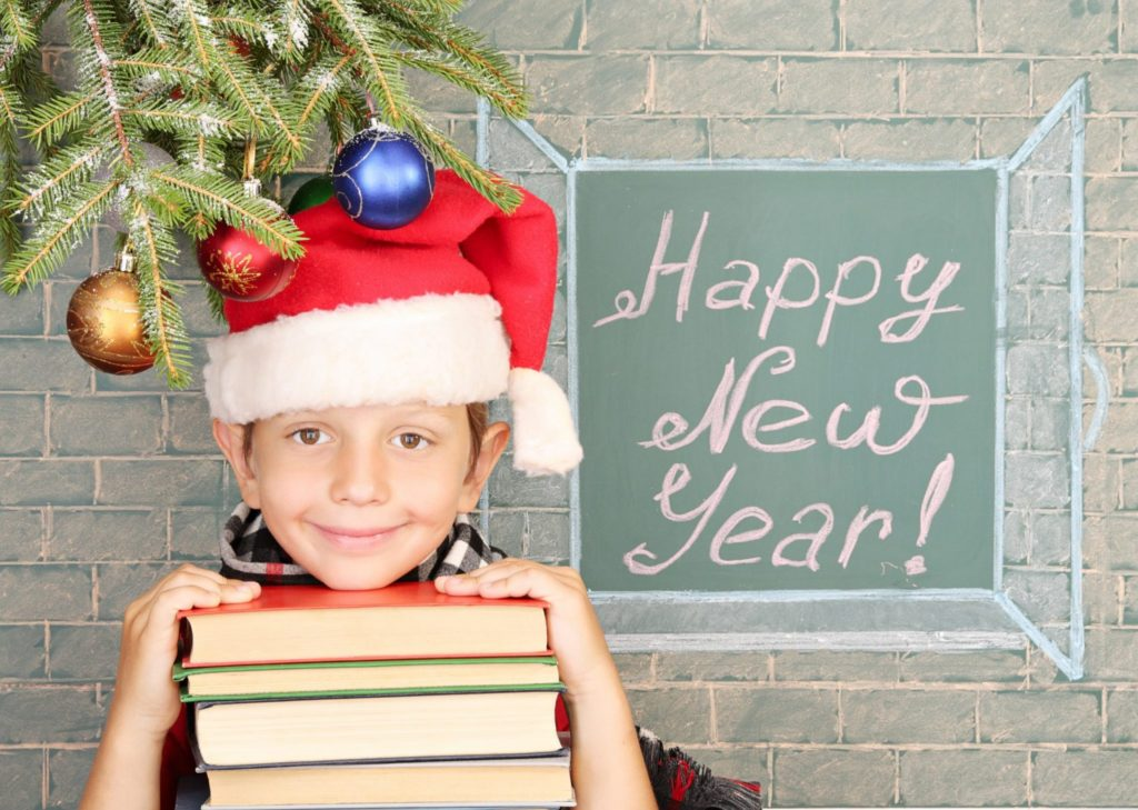 "Christmas decoration, schoolboy and message on chalkboard ""Happy New Year!"""