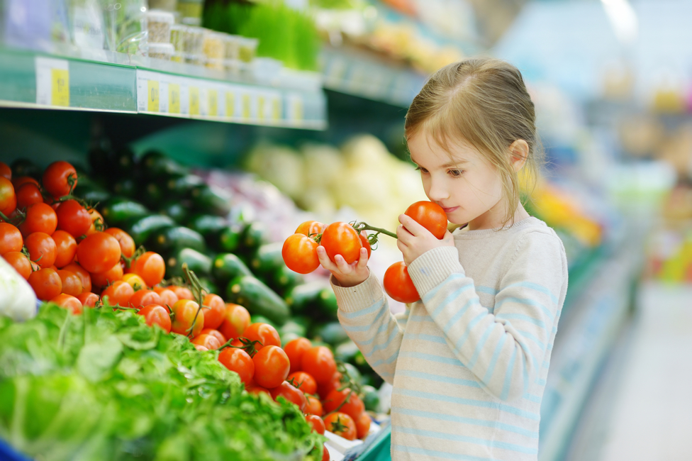 Little girl choosing tomatoes in a food store or a supermarket