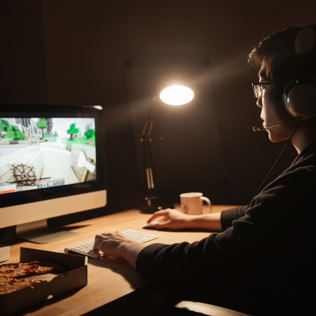 Man gamer in headset playing computer game and eating pizza in dark room